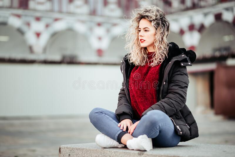 Curly blonde woman sitting on bech. Casual clothes.  royalty free stock photos