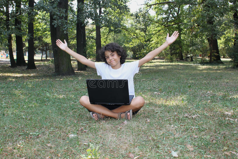 A curly boy with a laptop royalty free stock photo