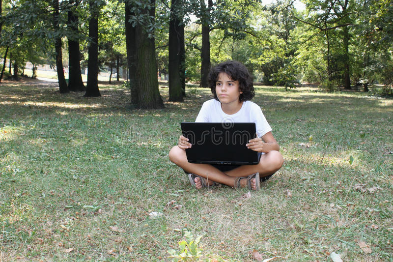 A curly boy with a laptop stock image