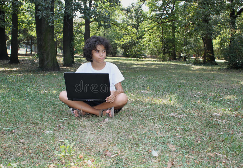 A curly boy with a laptop royalty free stock image
