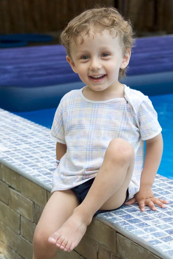 Curly boy at a pool (16). A curly white boy sits on skirting at a pool and smiles royalty free stock image
