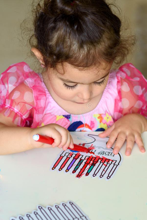 Curly brunette cute little toddler girl painting with color pen paper menorah and candle Jewish holiday Chanukah. royalty free stock image