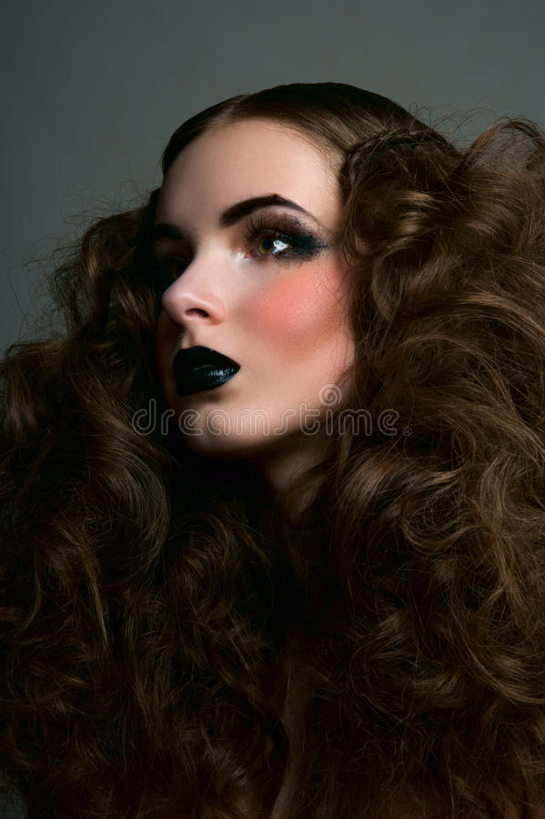 Curly brunette girl with black lips stock photos