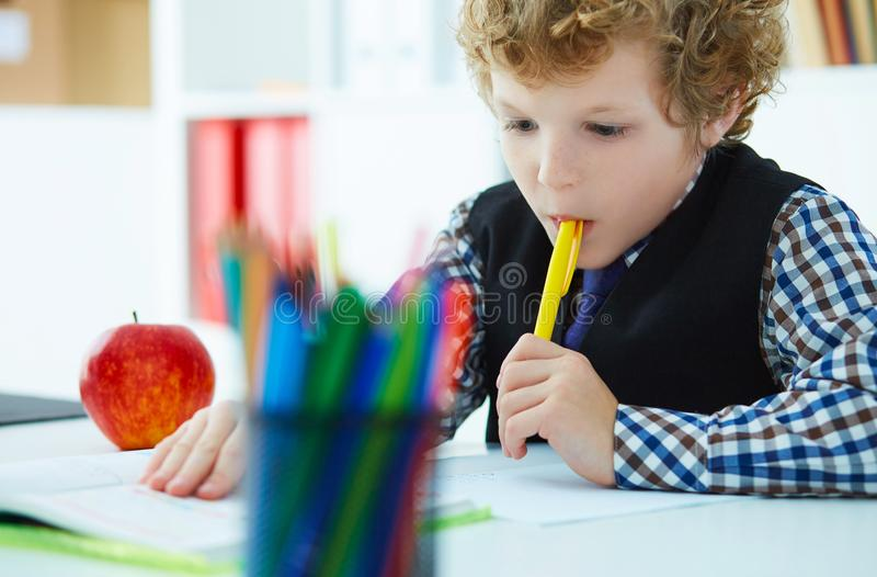 Curly Caucasian boy thought about the task and took a pen in his mouth during the lesson at school. Education, childhood royalty free stock image