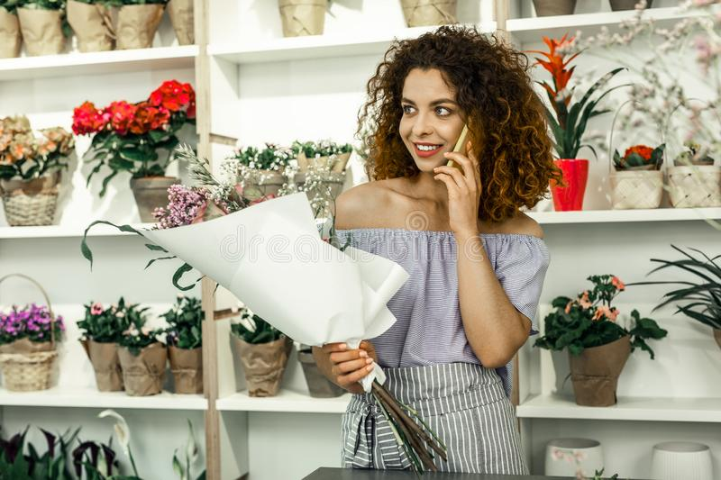 Curly florist calling her boyfriend while having break from work royalty free stock photos