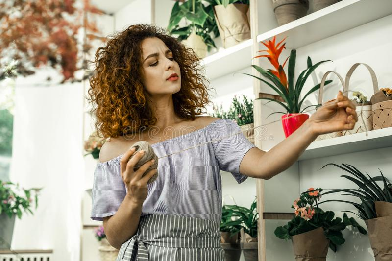 Curly florist looking at beige thread while making bouquet for client royalty free stock photo