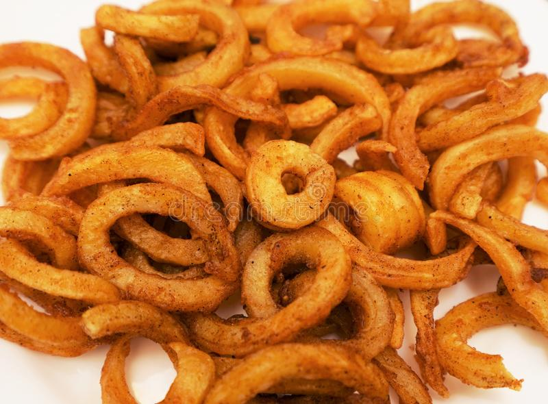 Curly Fries. Crisp and flavorful curly fries on white background royalty free stock images