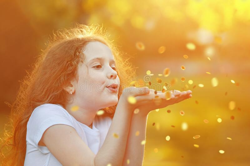 Curly girl blowing gold confetti with her hand royalty free stock photo