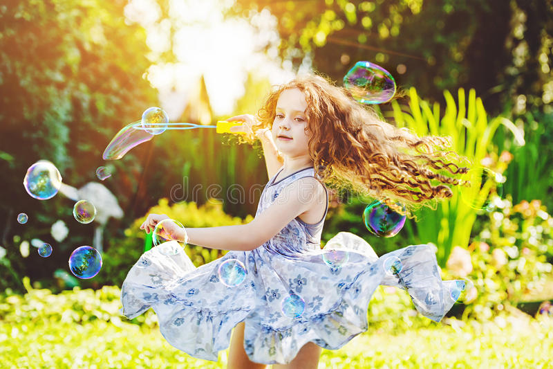 Curly girl in flying dress playing with soap Bubbles. stock photos