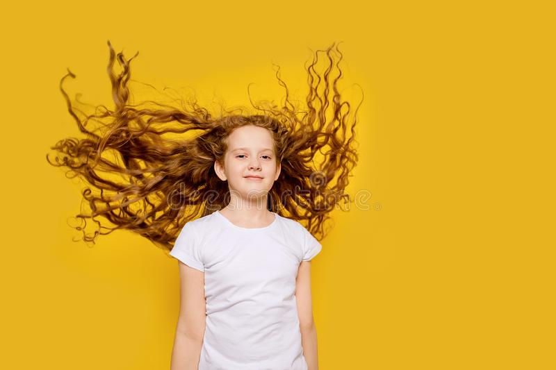 Curly girl with flying hair, studio shot on a yellow background stock photos