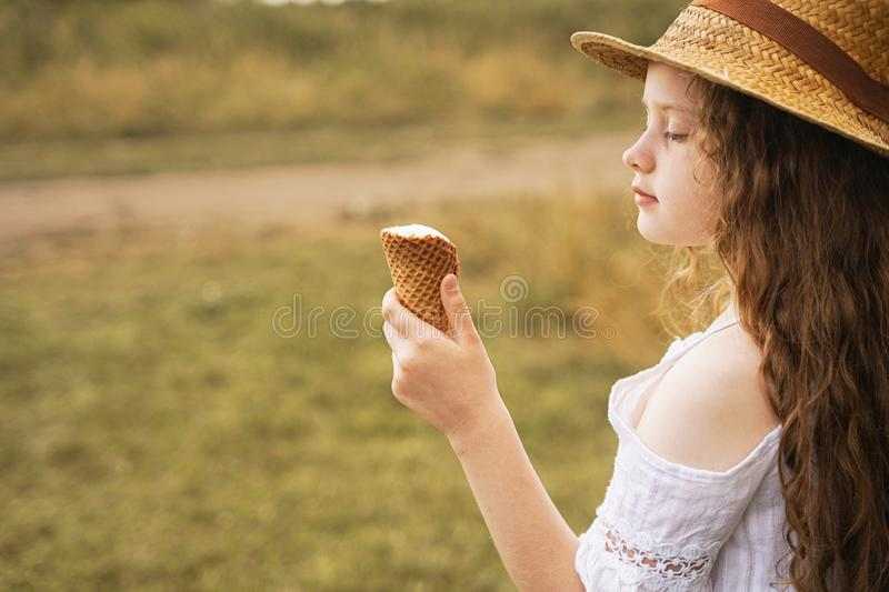 Curly girl in a straw hat eats ice cream in the village in the summer. royalty free stock images