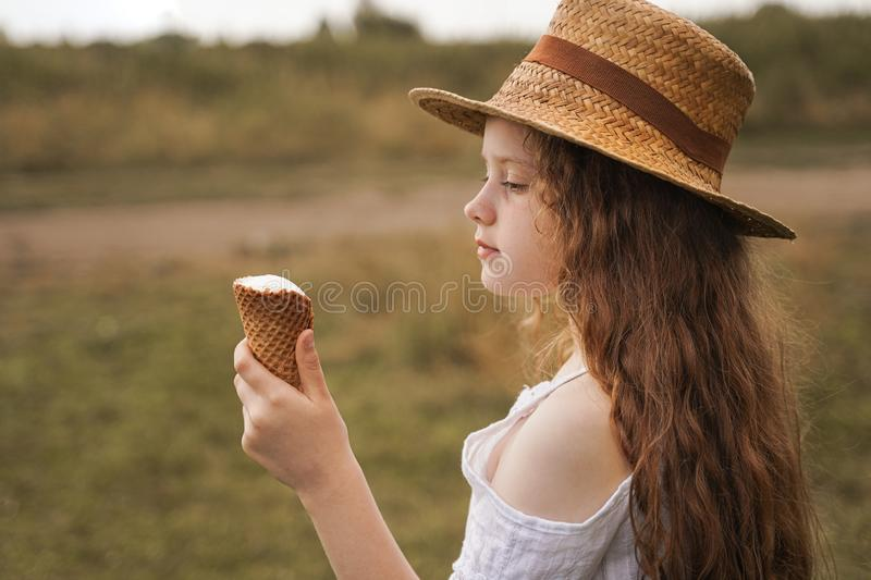 Curly girl in a straw hat eats ice cream in the village in the summer stock photo