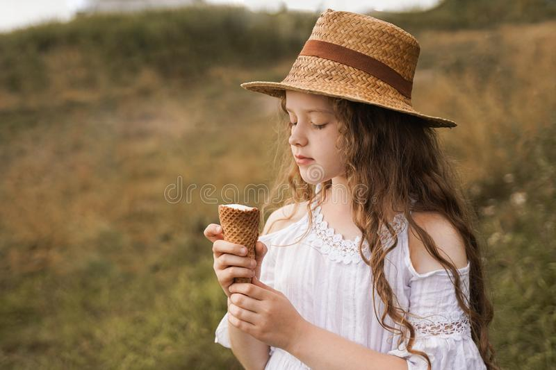 Curly girl in a straw hat eats ice cream in the village in the summer..Retro vintage, happy childhood concept stock image