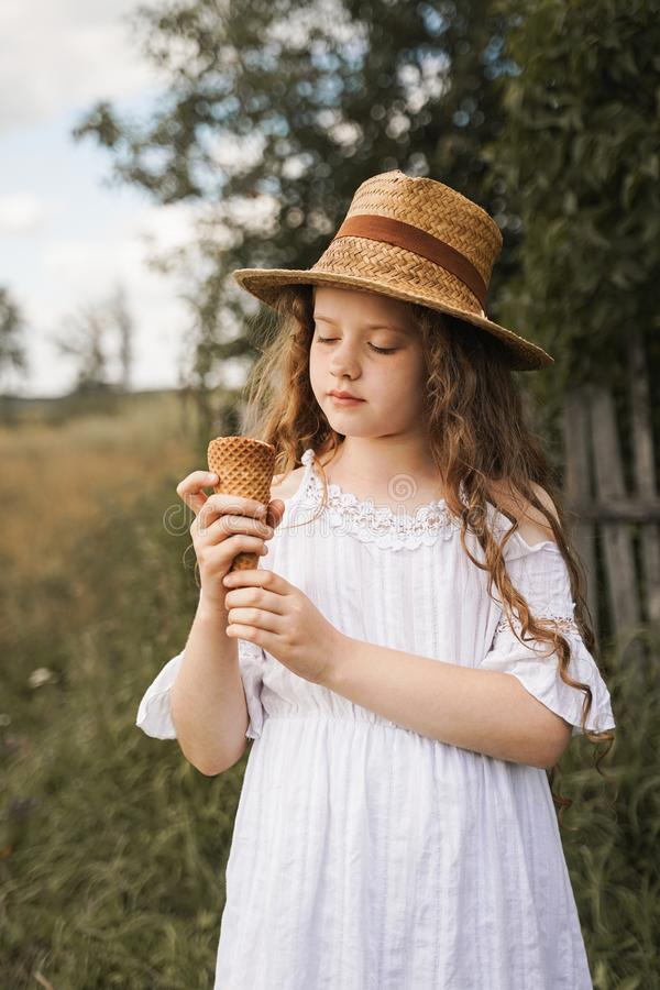 Curly girl in a straw hat eats ice cream in the village in the summer. royalty free stock photo
