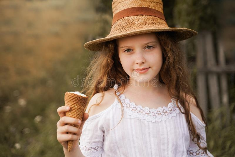 Curly girl in a straw hat eats ice cream in the village in the summer. stock photo