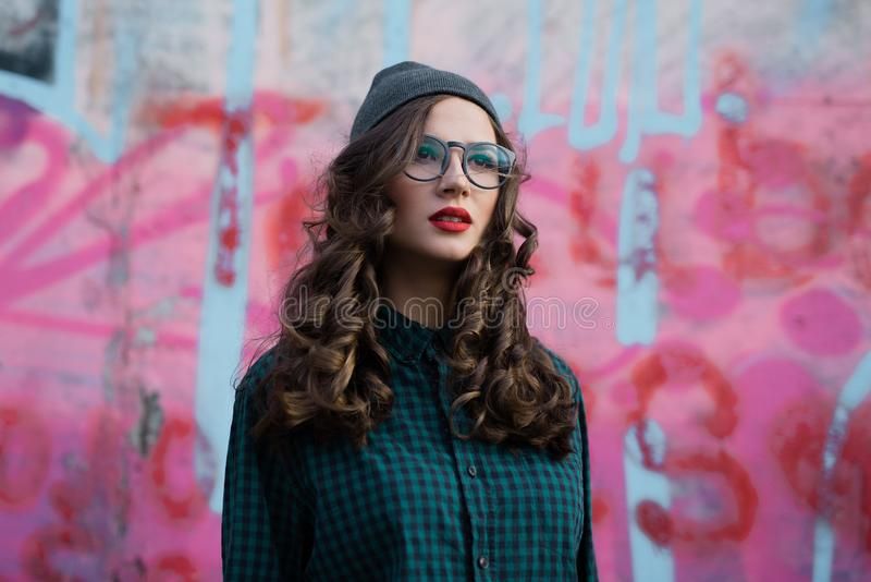 Curly girl with transparent glasses, pink backround stock photos