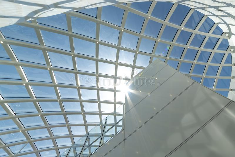 Abstract architectural structure on blue. Curly grid shape glass ceiling under a bright sunny blue sky abstract royalty free stock photo