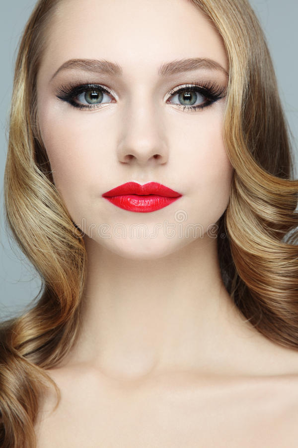 Curly hair. Portrait of young beautiful blond girl with red lipstick and stylish hairdo royalty free stock photography