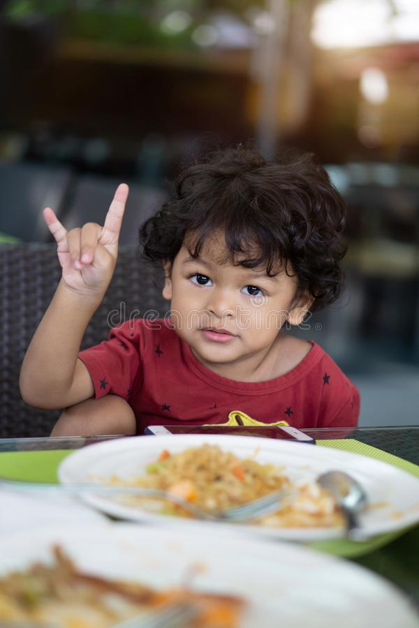 Curly hair asian child eating breakfast in a restaurant stock photos