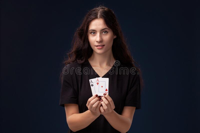 Curly hair brunette is posing with playing cards in her hands. Poker concept on a black background. Casino. stock photo