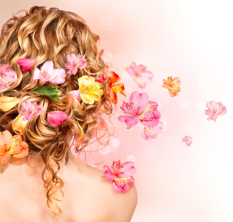 Curly hair decorated with flowers. Beautiful healthy curly hair decorated with flowers royalty free stock photo