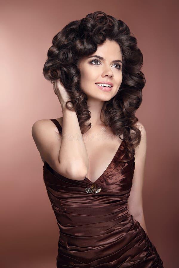 Curly hair. Happy smiling girl, brunette woman in brown elegant royalty free stock photo