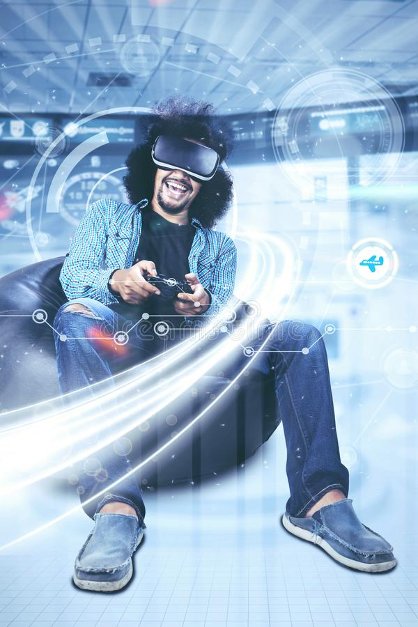 Curly hair man plays video game in futuristic screen royalty free stock photography