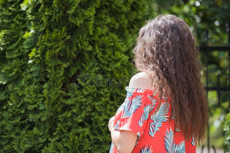 Curly hair on the street, background. Close up portrait of a young beautiful woman with long brunette curly hair posing against stock images