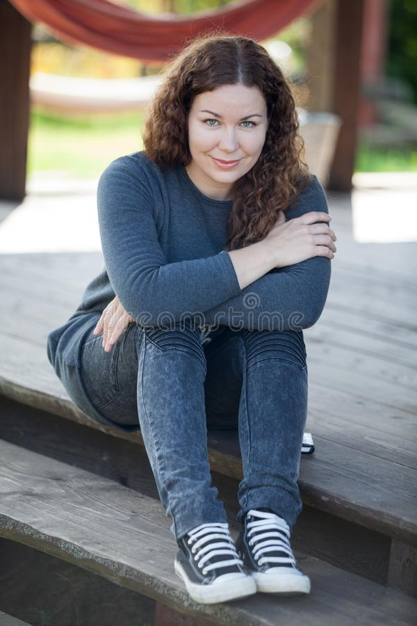 Curly hair young woman sitting on wooden steps of terrace of country house, portrait stock images