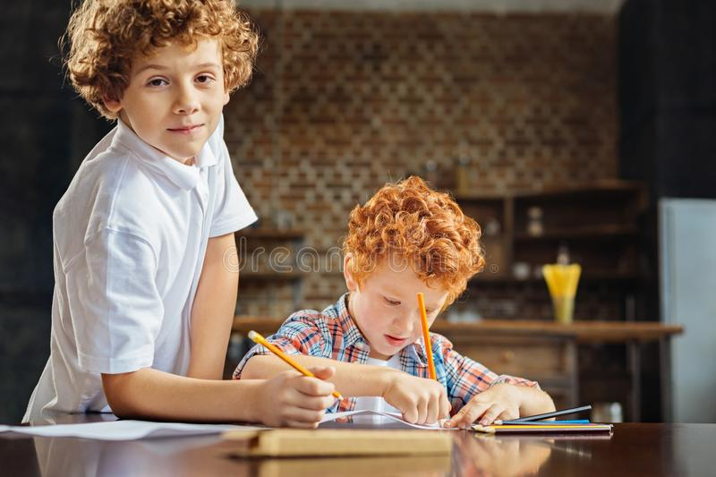 Curly haired brothers drawing together stock images