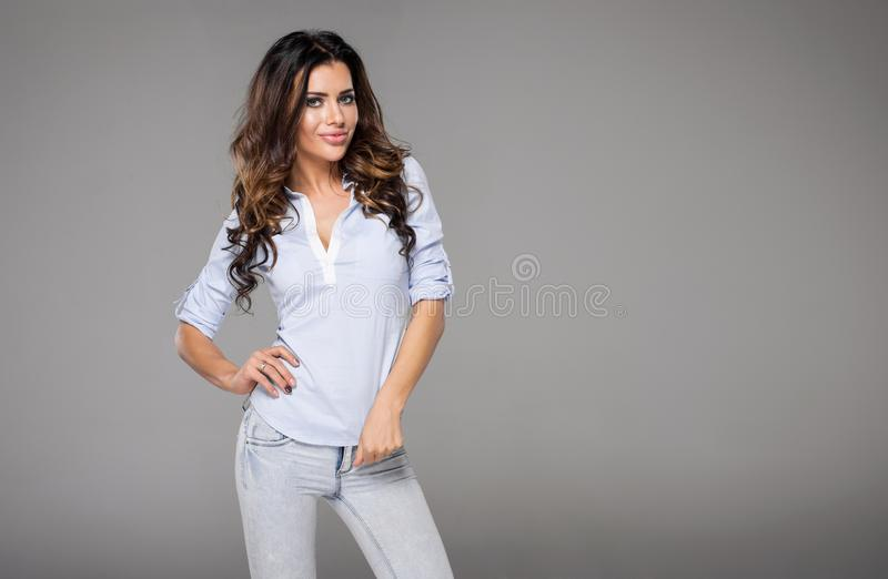 Curly haired brunette woman. A curly-haired brunette woman in jeans and collared shirt on a gray studio background royalty free stock photography