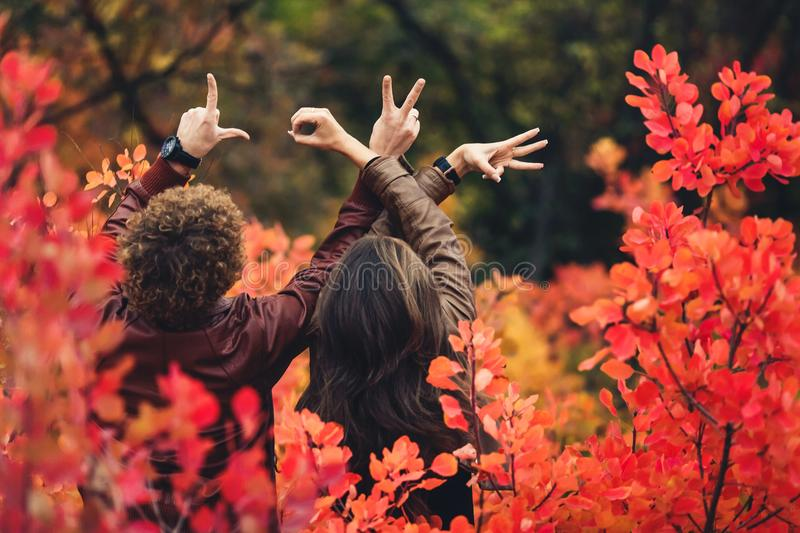 Curly-haired man and woman are standing with their backs among red autumn bushes and show gestures with their hands. royalty free stock photo