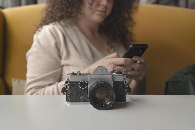 Curly haired photographer woman resting in a cafe. Curly haired photographer woman resting royalty free stock photo