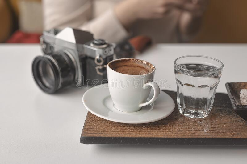 Curly haired photographer woman is resting in a cafe and drinking Turkish coffee. Curly haired photographer woman is resting stock image