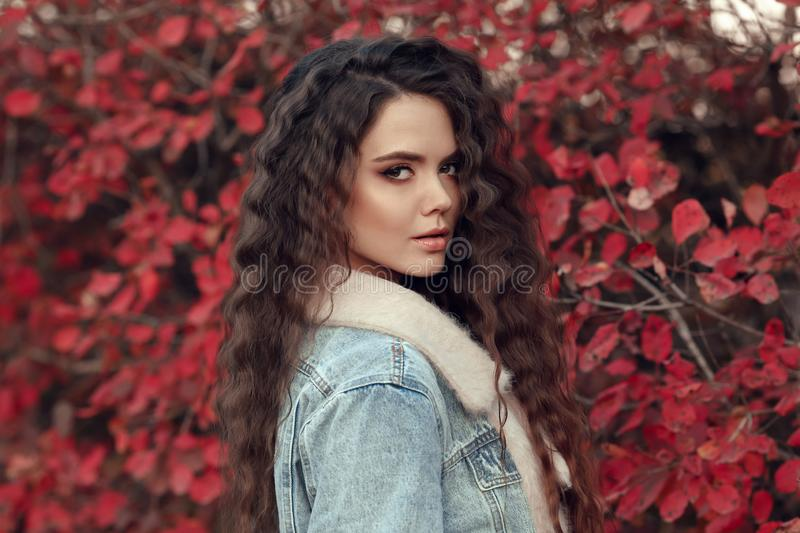 Curly haired Woman autumn outdoor portrait. Young beautiful brunette in jeans jacket with fur collar posing in red leaves park. A royalty free stock image