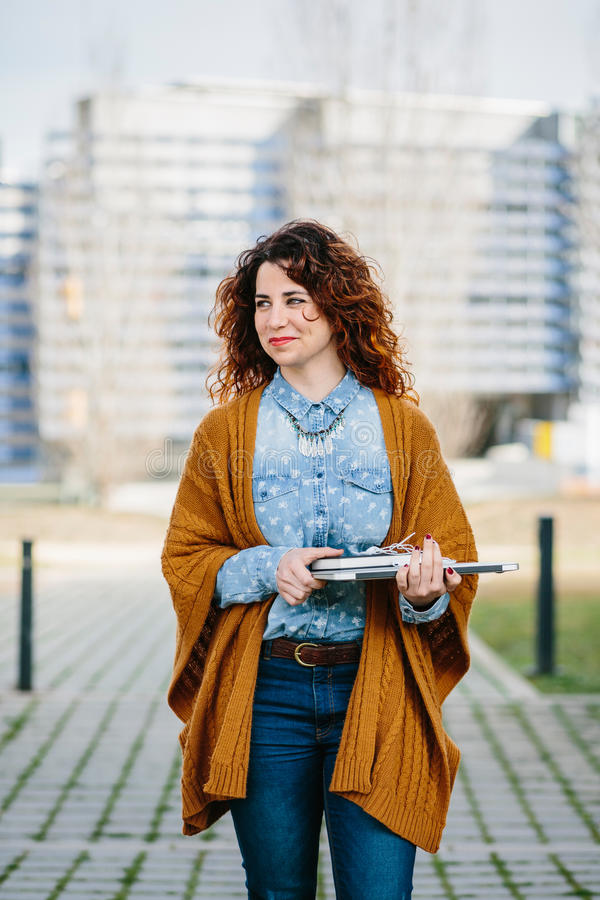 Curly haired woman walking the street while holding laptop. Smiling curly haired woman walking the street while holding laptop. Cityscape on background stock photography