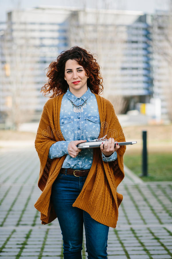 Curly haired woman walking the street while holding laptop. Smiling curly haired woman walking the street while holding laptop. Cityscape on background royalty free stock photography