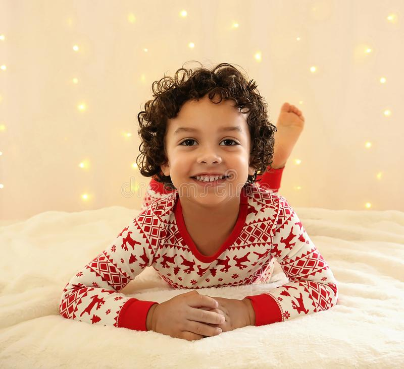 Curly haired young boy smiling at the camera. stock photos