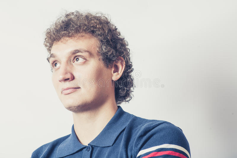 Curly haired young man on gray background with pensive expression. Curly haired young man on gray background with blank expression. Looking up/ Crossprocess stock images