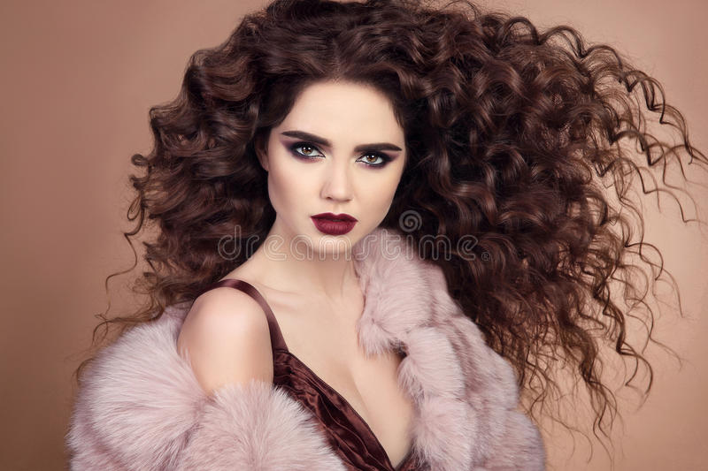 Curly hairstyle. Fashionable elegant woman with makeup and blowing healthy long hair posing in pink fur coat isolated on beige ba. Curly hairstyle. Fashionable stock images
