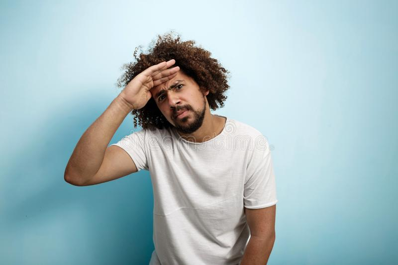 A curly-headed brunet man holding his palm over the forehead is looking concentrated and serious. Short beard and thick. Eyebrows royalty free stock photo