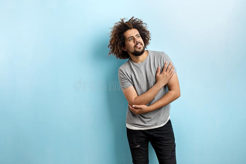A curly-headed handsome man wearing a gray T-shirt and ripped jeans is standing and thinking with his hand on the chest royalty free stock images