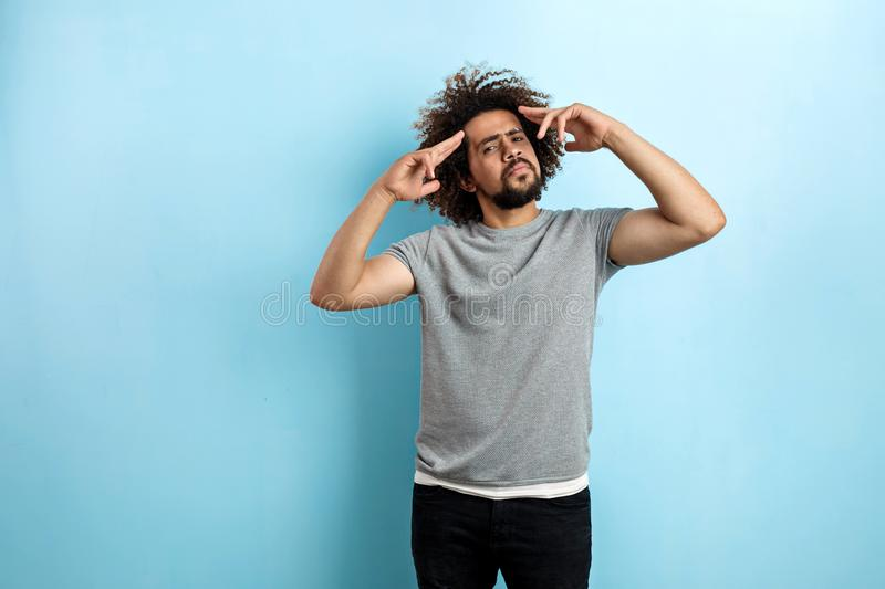 A curly-headed handsome man wearing a gray T-shirt is standing with a concentrated look and with his hands raised to the. Forehead over the blue background stock image