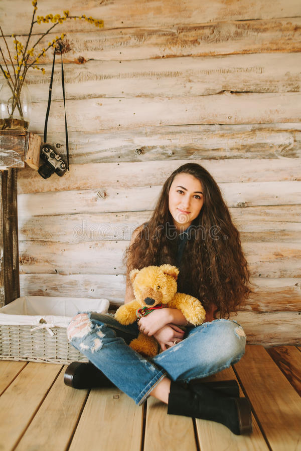 Curly hipster girl in tattered jeans on a wooden background.  stock photo