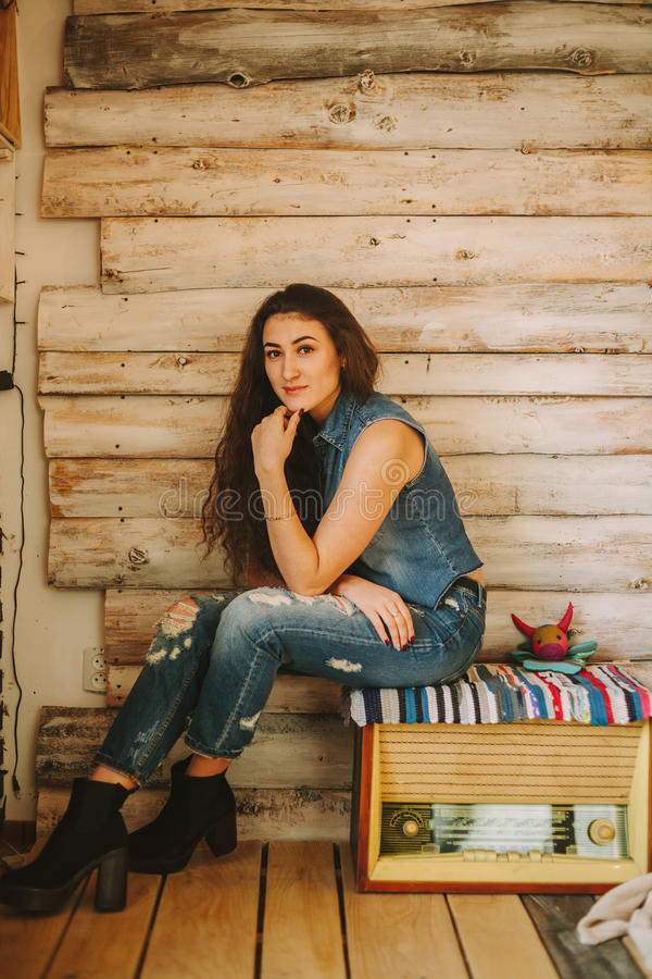 Curly hipster girl in tattered jeans on a wooden background. Curly hipster girl in tattered jeans on a wooden background stock photo