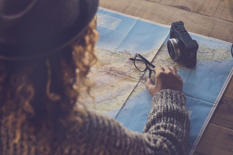Curly lady viewed from rear planning next trip vacation wanderlust on a paper map and old camera on the table - planning holday stock image