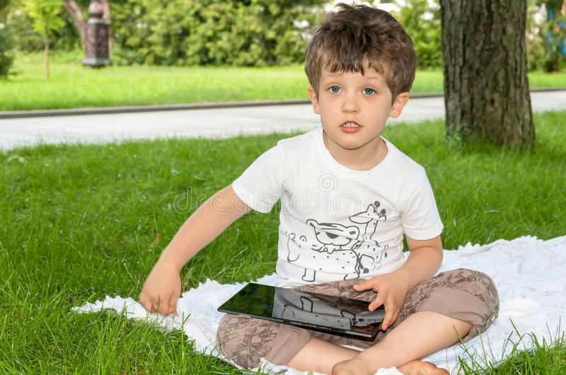 Curly little boy playing on a tablet and looking directly royalty free stock photo