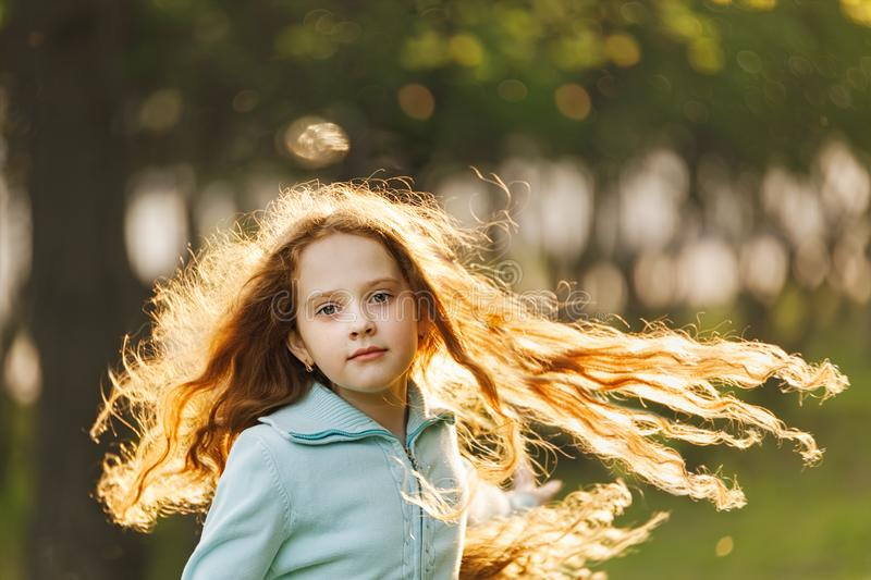 Curly little girl with flying redhead hair royalty free stock photo