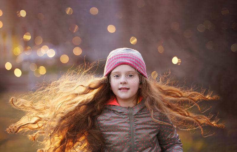 Curly little girl with flying redhead hair. royalty free stock image