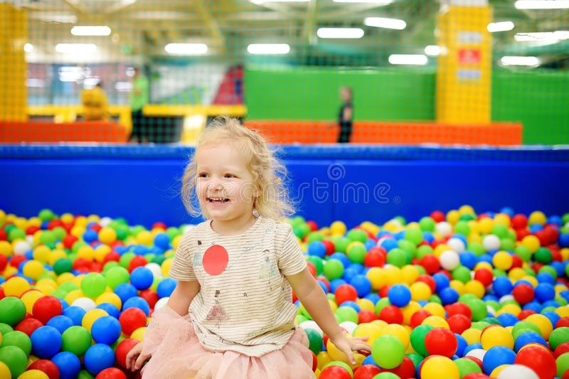 Curly little girl having fun in ball pit with colorful balls stock photos